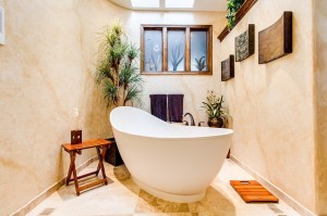 A bath tub sits in int he middle of the room. It is taller than the standard bathtub and sculpted into a shape with high ends with thin sides.