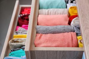 Carefully folded washing placed neatly into drawers.