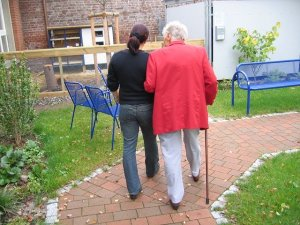 An older woman in a red jacket uses a cane to walk with a younger woman along a pathway.