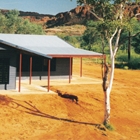 A small house with a large veranda sits on orange soil in a remote location.