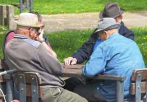 Four older men wearing hats sit at a square table in the park.