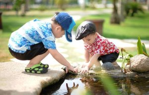 Two small boys are crouched by the side of a pond and are reaching into the water.
