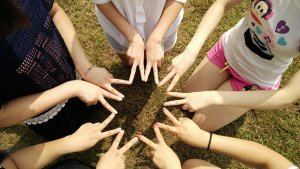 A group of young women stand in a circle with their forefingers and middle fingers spread out and joined up to make a star shape.