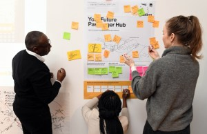 Three people are in front of a workboard with lots of coloured post-it sticky notes attached.