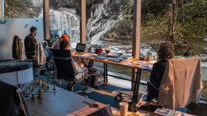 A workbench with computers overlooks a waterfall and stream. People are looking out of the window. Biophilic design is for everyone.