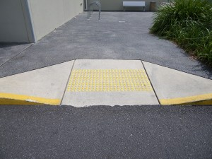 A concrete kerb ramp with yellow tactile markers on the slope.