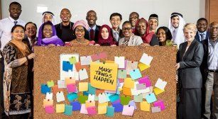 An international group of adults stand with a big board in front of them. It says, Make Things Happen. There are lots of coloured post it notes on the board.