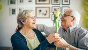 A older man and woman are smiling at each other. The man is handing the woman a yellow tulip.