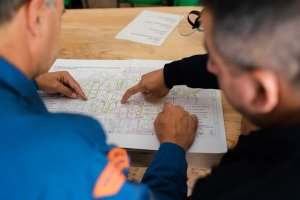 Two construction men sitting at a table look at a complex engineering diagram.