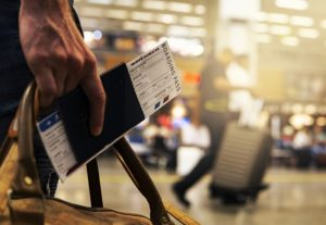 A man holding a boarding pass in his hand along with a bag. You can see the airport in the background.