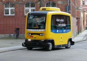 A yellow autonomous vehicle on the road. It is box shaped with large windows and small wheels.