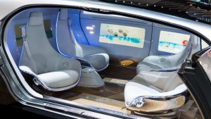 Side of an autonomous vehicle is cut away to show four seats in pairs facing each other.