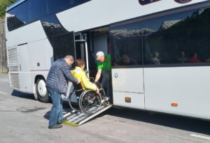 A woman in a yellow jacket is being assisted onto the tour bus by two men up a ramp.