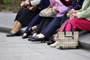 The legs and feet of six older women are shown sitting on a stone wall. They are holding their handbags in their laps. They are wearing sensible shoes.