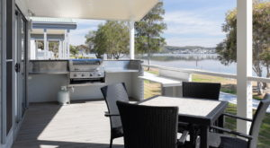 A view of the deck with a barbeque and outdoor seating. The deck overlooks the Lake.