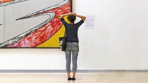 A photo of a woman standing with her back to the camera, looking towards a contemporary painting, suggesting that providing supplementary sources of information to complement visuals can reduce barriers to learning.