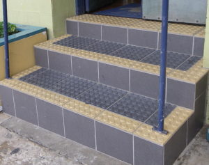 Three steps into doorway are tiled with grey hazard tactile markers edged with yellow markers.