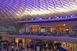 Inside Kings Cross Railway Station in UK showing two floors with shops inside a giant atrium.