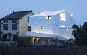 rear view of the all white home at twilight. It shows the ramp coming up from ground level on one side wrapping around the back and up to the first floor on the third side.