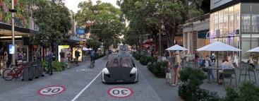 A streetscape of the future with street plantings, outdoor eating and a driverless car in a 30 kph zone.