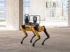 A robot with four yellow articulated legs stands on a bare concrete floor in a half finished building.