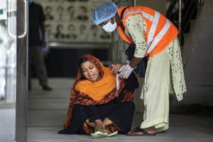 A woman is sitting on the ground and is being helped by a person in protective clothing and a hi vis vest. The woman looks distressed.