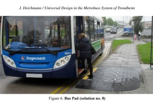 A woman is getting on a bus. The footpath has a built up pad to raise the height so she can get on the bus. When universal design isn't enough.