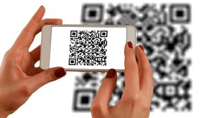 A woman holds a smartphone over a QR code. It makes for smart cities.