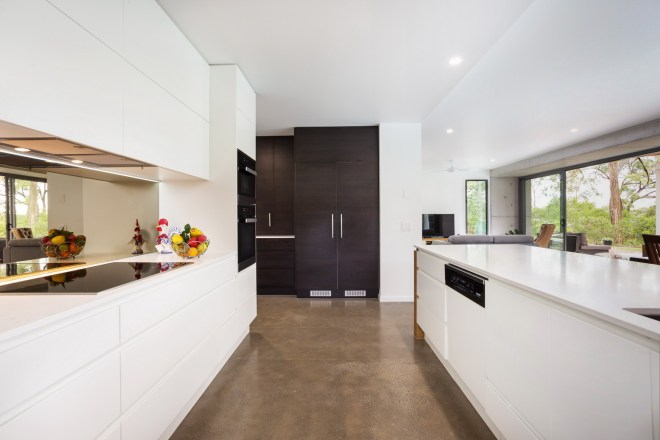 Kitchen with white benches contrasting with the light brown floor.