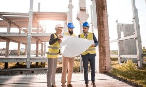 Three men in hard hats stand on a building site looking at architectural design plans.
