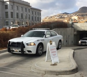 2 Utah State Trooper vehicles exit the parking garage as other trooper cars exit out the back with the arrested protestors in custody.