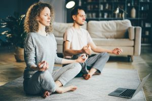 Calm couple in pajamas meditating, sitting on lotus pose at home.