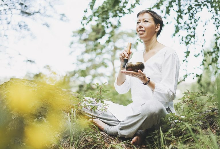 Young smiling woman playing on the brass Tibetan singing bowl in forest