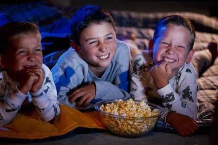 Tre bambini guardano un film divertiti