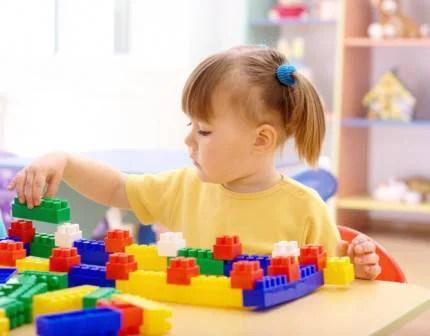 Bambina gioca con mattoncini colorati