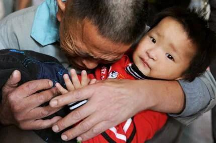 Foto di un papà che abbraccia il figlio rapito e poi salvato