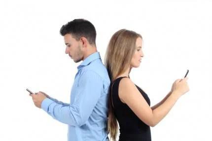 Coppia di spalle ognuno con smartphone