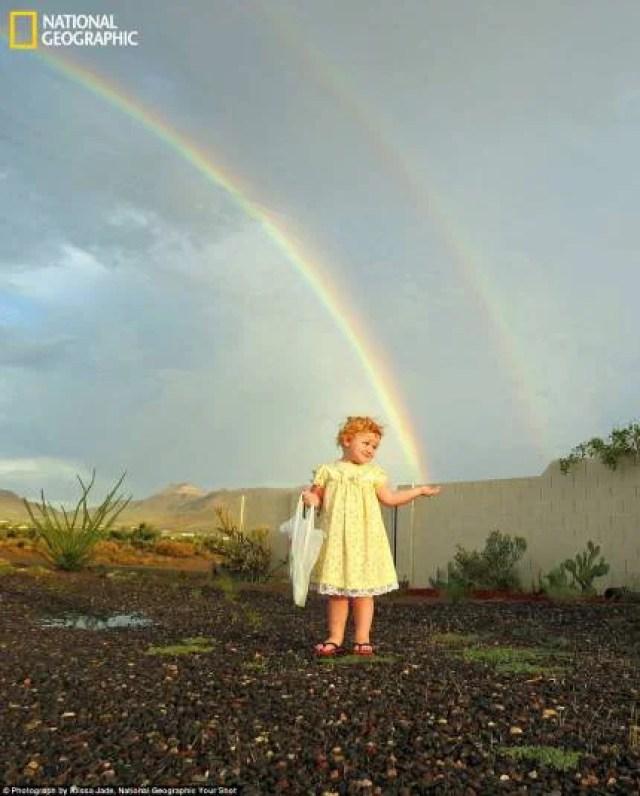 bambina di circa tre anni in abito bianco , sullo sfondo doppio arcobaleno. la mono della bambina sembra tenere un capo di arconbaleno