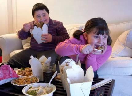 fratello e sorella in sovrappeso seduti sul divano davanti alla tv mangiano cibo da asporto