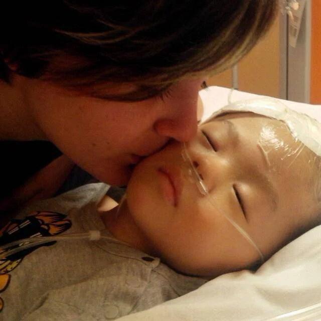 bambino malato baciato da una donna
