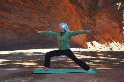 Mujer de 67 años practicando yoga al aire libre- Virabhadrasana B