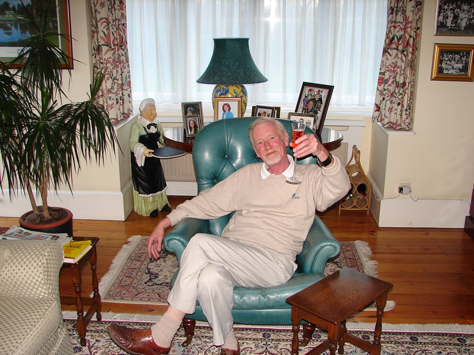Phone of a tall man, legs crossed, sitting in a great chair, holding up a glass of wine. He's seated in a living room with family photos and a lamp in the background.