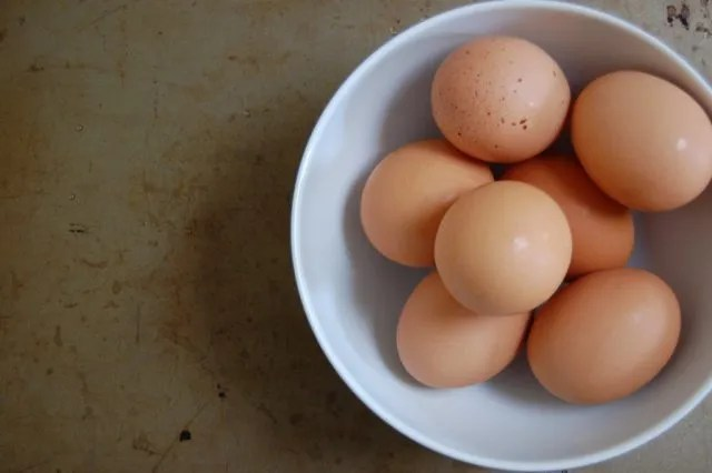 bowl of brown eggs on rustic background