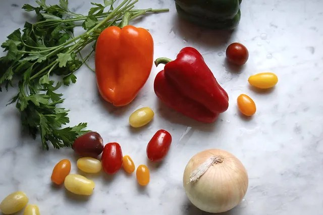 bell peppers grape tomatoes onion parsley on marble