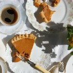 slices of pumpkin pie on table with coffee and forks