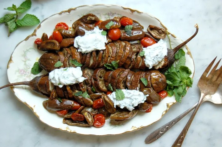 platter of hasselback eggplant parmesan with mint and tzatziki and serving utensils