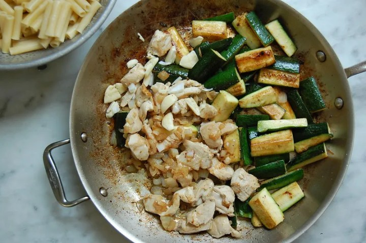 pan of zucchini with chicken and onion pieces on marble