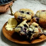 plate of blueberry muffins with butter on wood plate