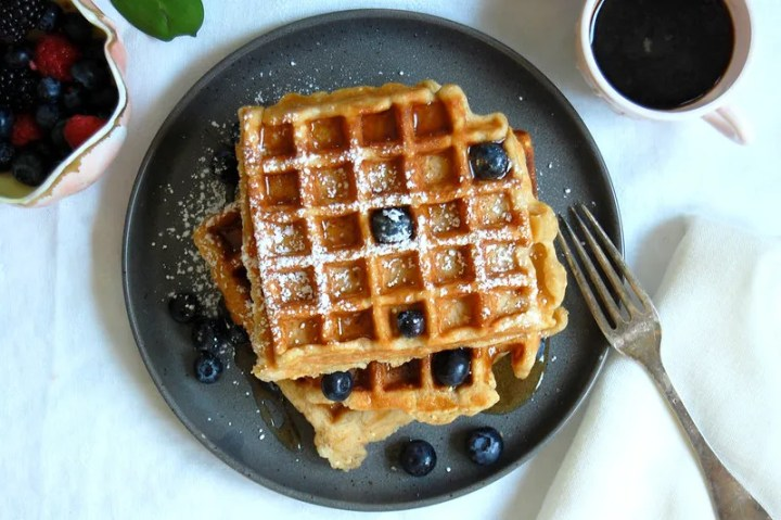 overhead stack of whole wheat buttermilk waffles on gray plate with blueberries