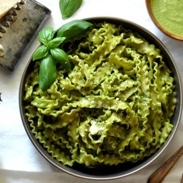 overhead shot of pesto recipe pasta with basil and cheese